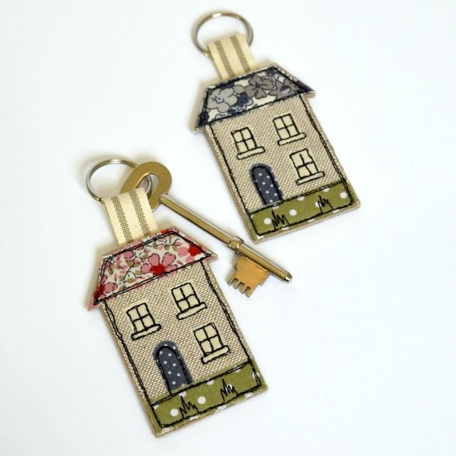 Handmade fabric house-shaped keyring decorated with applique and embroidery and a pink floral roof.