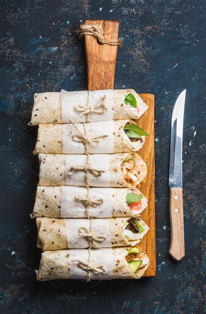#Tortilla wraps on serving board  Tortilla wraps with various fillings on wooden serving board and knife over dark blue plywood background top view vertical composition. Healthy snack or take-away lunch bites