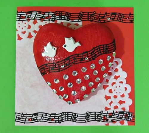 Paint a polystyrene heart red, add some diamond bling stickers to the heart, and adhere the heart to the front of a card. When you are in love, it feels as if your heart is singing, so add some spirited musical notes. This red Valentines heart that pops will show your valentine just how much you love him. #FaveCrafter