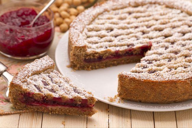 La Linzer Torte è una gustosa crostata preparata con farina di nocciole tritate e farcita con confettura di ribes.