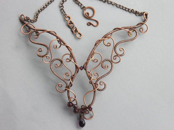 Copper free form scroll work adorns each side of this gemstone necklace with Amethyst stones and Swarovski crystals clustered at the bottom.