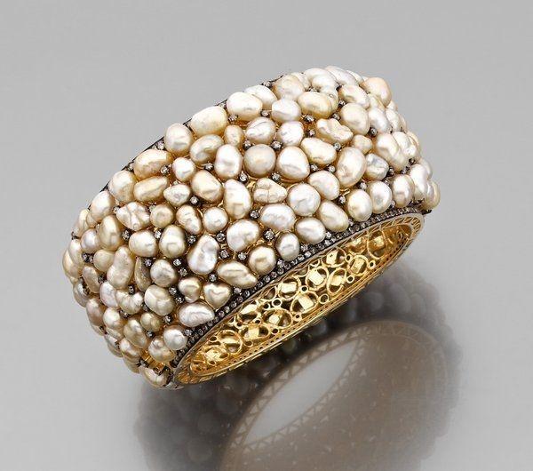 Large bracelet manchette ouvrant en or jaune à motif ajouré entièrement serti de perles baroques blanches et jaunes alternées de petits diamants, le bracelet est bordé de lignes de diamants bruns.Photo courtesy Artcurial