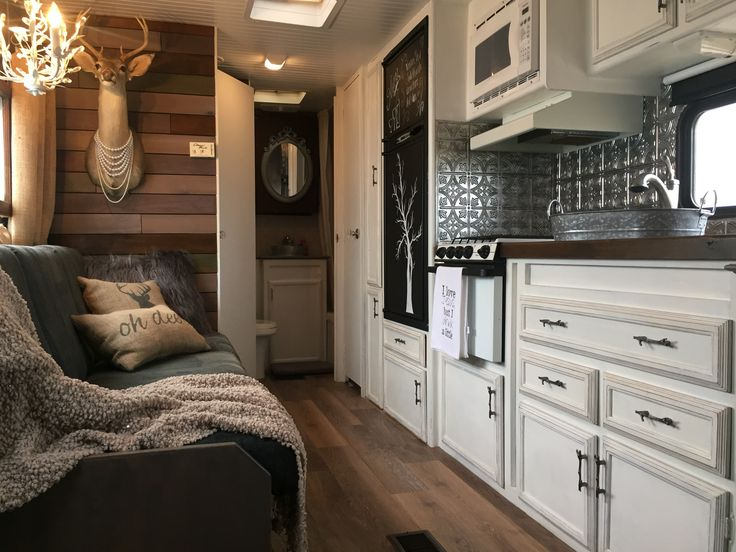 Wood accent wall, glam mirror, comfy couch and throw.