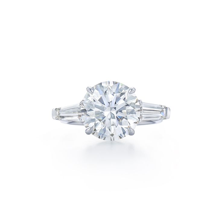 Round brilliant diamond ring with tapered baguette side stones. Set in platinum. Kwiat Round Brilliant Diamond Engagement Ring | style # 17600A | Kwiat