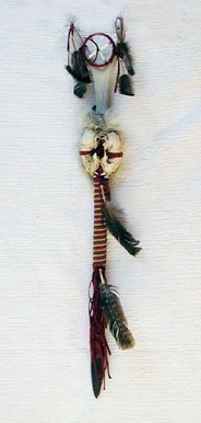 """Cherokee Made Skull Trail Marker 40"""". The trail marker is used by a clan or family to mark a trail. The colors on the trail marker are the clan colors. Deer antlers represent family and gentleness. A medicine wheel is placed between the horns to protect the family from harm and misfortune. Coyote skulls represent wisdom and folly. Feathers represent a connection with prayer and protection. They hold and carry all your dreams and prayers and protect you and your family.  $129.95"""