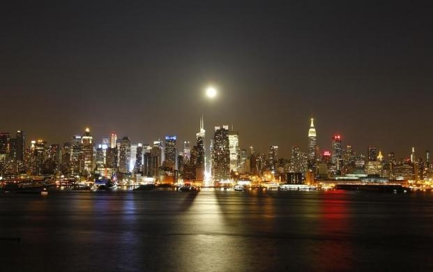 A full moon rises over the skyline of New York City above 42nd Street (C), as seen across the Hudson River in Weehawken, New Jersey April 25, 2013. REUTERS-Gary Hershorn