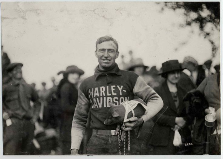 """HOGS: Ray Weishaar and the Harley-Davidson team mascot """"piggy"""" in 1920."""