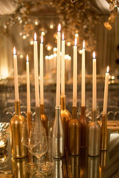 Candles placed in wine bottles, a delightful 50th birthday decorating idea. Spray paint wine bottles golden, and use as decor. Beautiful!