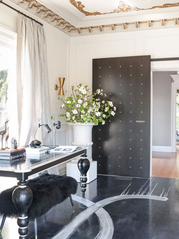 Desk: Large black wood desk with white accents from Coup d'Etat.Door: Oversized barn door panels in ebonized wood finish, with bronze pyramid studs.   - Veranda.com