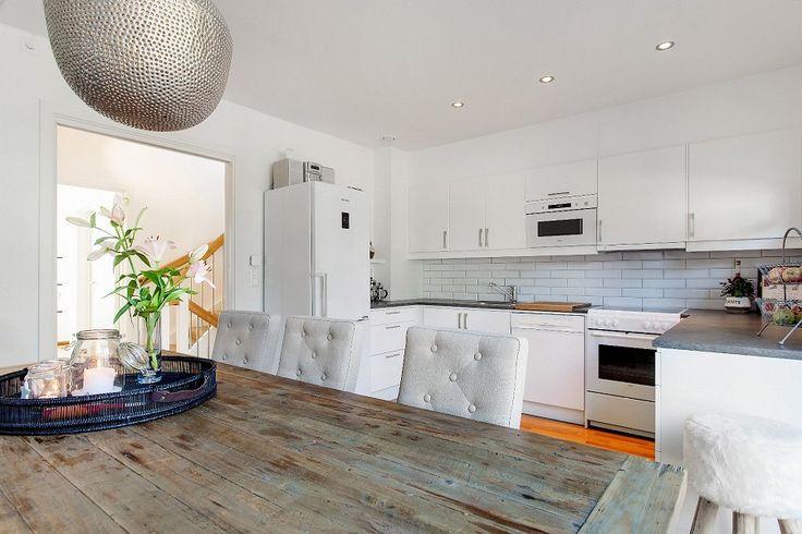 Stort og innbydende kjøkken fra Drømmekjøkkenet med hvite fronter, laminert benkeplate og mye skap.