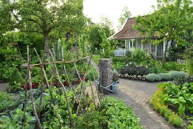 Claus Dalby calls this a romantic vegetable garden. Rustic supports for vining crops are featured..