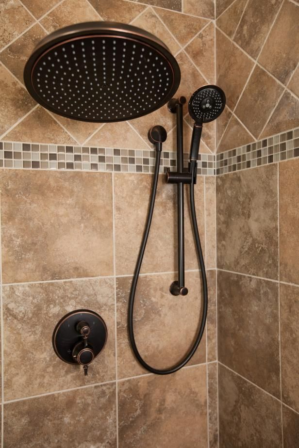 This renovated bathroom now has a contemporary style with an oversized shower head earthy-brown tiled shower walls, as seen on HGTV's Property Brothers.