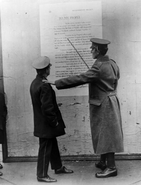 WWI; A soldier points out a passage in a poster showing the 'King's Appeal' which asks his 'subjects' to volunteer to fight .