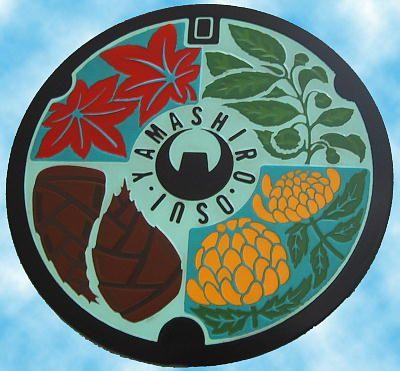 木津川市(山城町) 町の木「もみじ」、町の花「菊」、町の特産品「お茶」「タケノコ」をデザインし、中央部に町章を配し、自然を大切にしうるおいのある活力ある町を表現したもの。