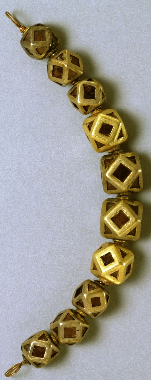 Ostrogothic polyhedral beads, part of a woman's necklace, gold with garnets over pitch, 5th century