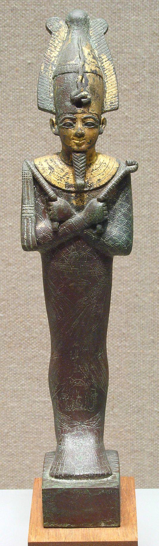 Osiris: Comenzó siendo un monarca civilizador que enseñó la agricultura y las artes a sus súbditos. Muerto por su hermano Seth una vez en los infiernos se convirtió en el soberano de los muertos y de la vegetación marchita.  Se le representa bajo formas múltiples, con el cetro y el látigo en las manos y con la corona blanca con plumas y cuernos, presidiendo en numerosas ocasiones el tribunal de ultratumba.  Marido de Isis, también es un dios de la fertilidad. Estatua en Bronce. Época tardía.