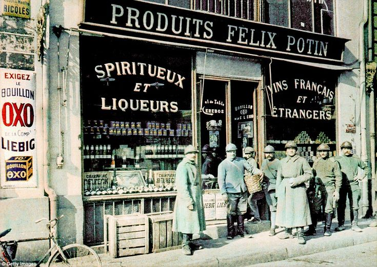 French soldiers in front of a grocery store, with signs advertising liquor and wine in the windows, in the market square in Reims in 1917
