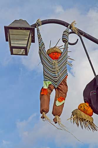 Scarecrows hanging from a lamp post