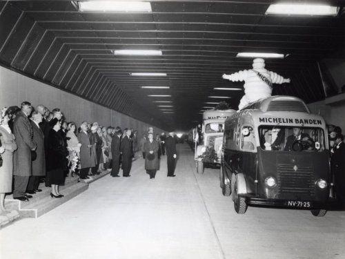 Verkeer, wegen, auto's. Michelin-auto met Michelin-mannetje (Bibendum) op het dak passeert koningin Juliana bij opening Velsertunnel. Velsen, 28 september 1957.