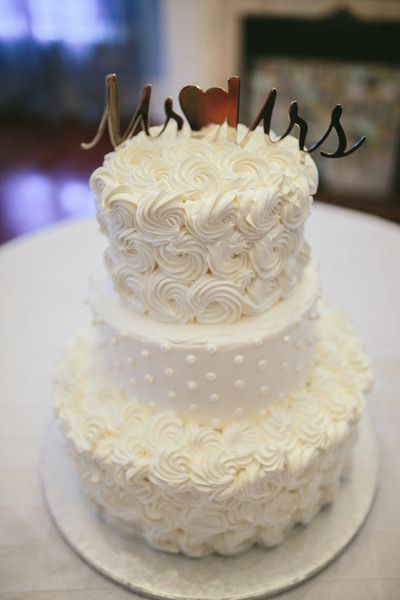 Three-tier wedding cake with piped rosette and polka dot details and gold cake topper {Brandy Angel Photography}