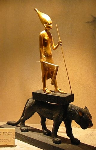 King Tut'ankhamun on a panther. Statuette of gilded wood from the king's tomb, showing him as king of Upper Egypt, carrying a flail in his hand and leaning upon a staff. A number of statuettes of this type, not more than two feet high, were found in the tomb.