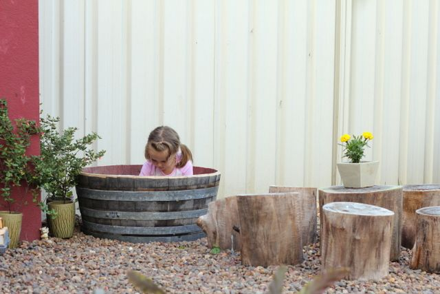 A sand play wine barrel next to the log table & chairs -- for a fun and easy outdoor kid play area!