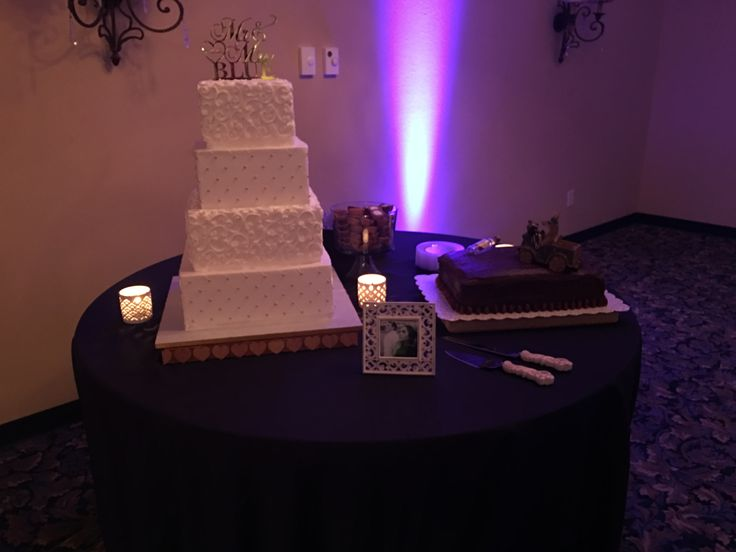 Wedding reception cake table with uplighting in the background. Bride and grooms cakes on display in the ballroom.