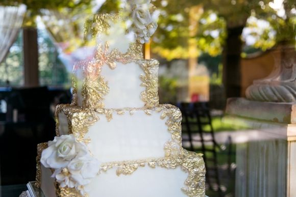 Inspired by the grandur of Tuscany's noble villas and castles, this ornate wedding cake with 24 carat gold gilded sugar frames and a raw silk embossed texture, brought us back to the Italian Renaissance. Square tiers and romantic sugar flowers balanced it out to give the whole cake a more contemporary feel. #tuscaweddingcakes