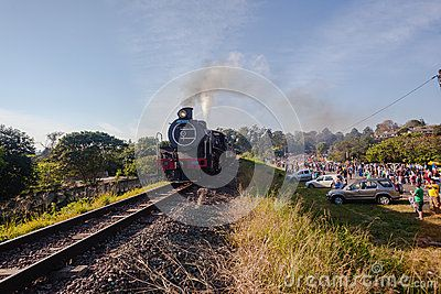 Steam train runs close the the old main road between Durban and Pietermaritzburg with the Comrades marathon running the same day with train spectators .