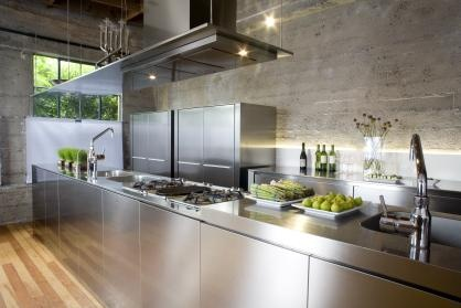 Everything old is new:  Sleek #stainless steel #cabinets contrast with sanded #concrete walls in this refurbished 1940s warehouse interior. #SanFrancisco home #interiordesign