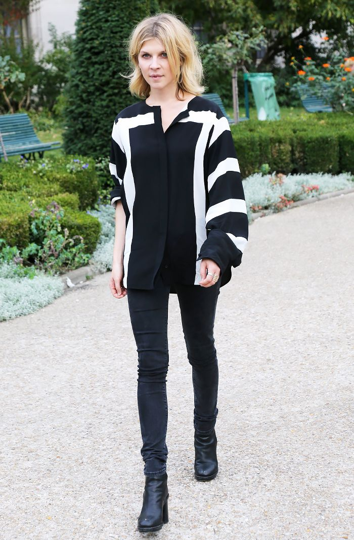 Clemence Poesy wearing a black and white blouse with black skinny jeans and black boots