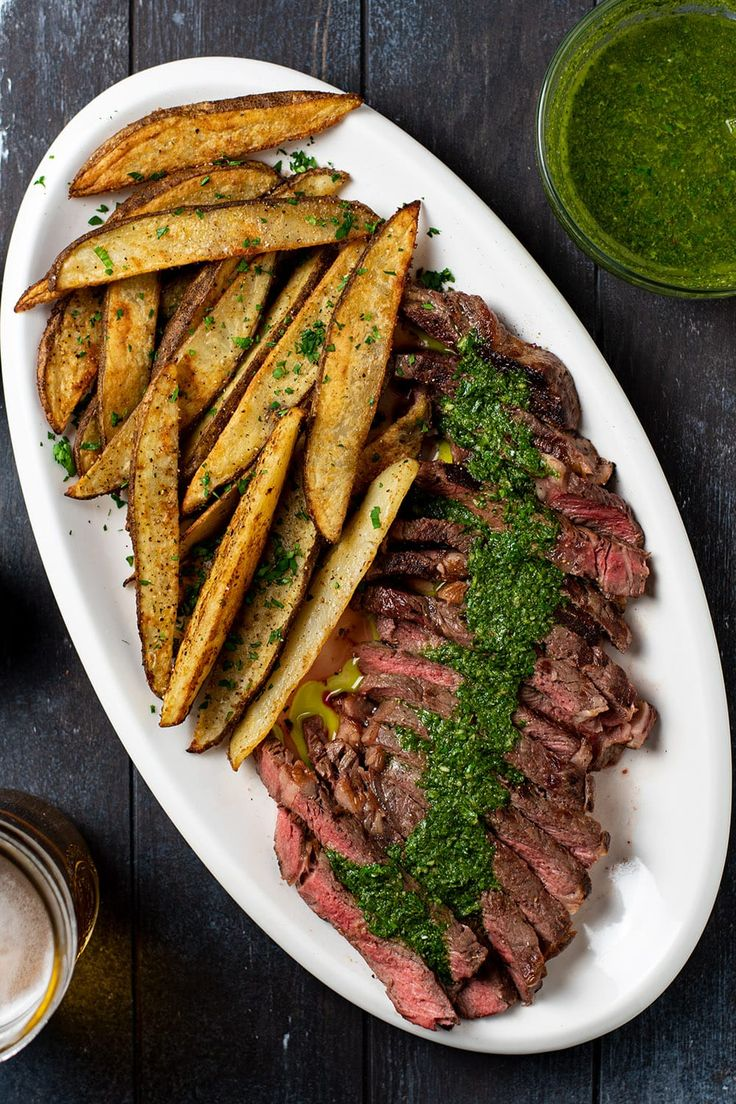 Steak frites recipe. Delicious pan-seared ribeye steak topped with homemade chimichurri sauce. Loaded with garlic, cilantro, and cumin, chimichurri will transform your sirloin steak into a Latin American dish and perfectly complement every bite. Served with crispy golden russet potato wedges seasoned with garlic powder, onion powder, paprika, salt, and pepper. It's the perfect blend of spices for fries. #steakfrites #steakandchimichurri #steak #chimichurri