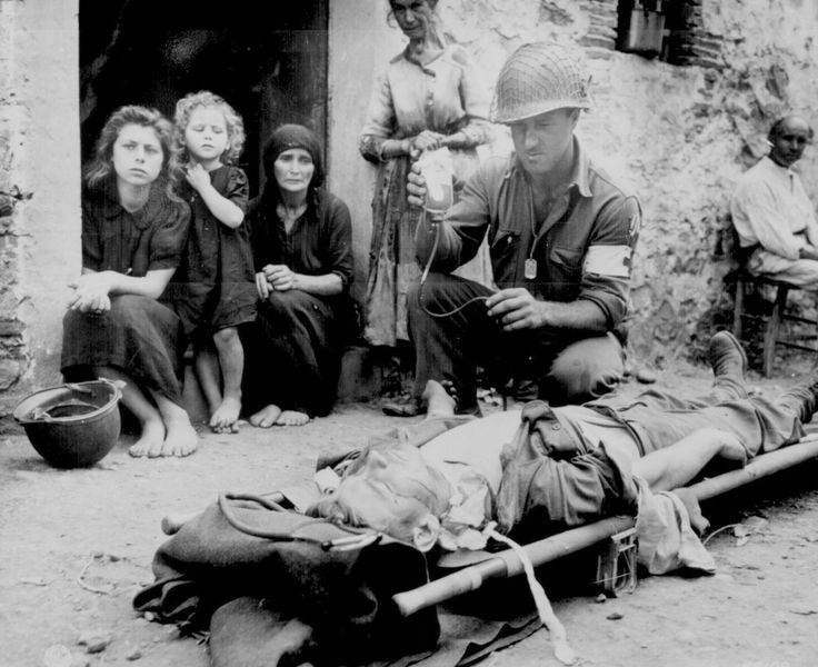 """Private Roy Humphrey is being given blood plasma by Pfc. Harvey White,  after he was wounded by shrapnel, on 9 August 1943 in Sicily."""""""