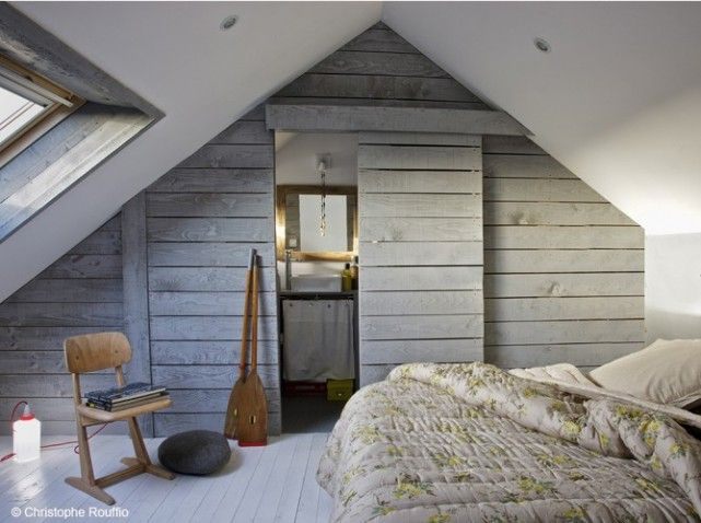 A Larmor-Plage, le décorateur Yann Falquero a recouvert les murs de la suite parentale de bardage en planches de bois grisé pour un bel effet déco.