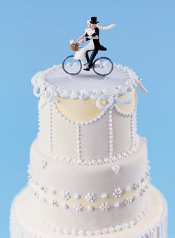 """Les mariés à vélo"" metal cake topper, about $30, Pixi Shop. Hummingbird cake made with pineapple, pecans, and bananas, filled with vanilla cream-cheese frosting and iced with fondant. Serves 75 as shown, $12 per serving, Lovin Sullivan Cakes."