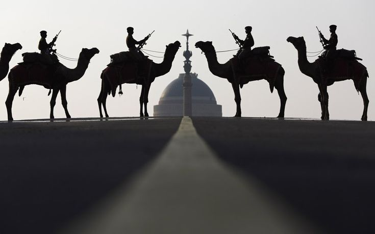 India's Border Security Force soldiers ride their camels in front of India's presidential palace Rashtrapati Bhavan during a rehearsal for the Beating the Retreat ceremony in New Delhi