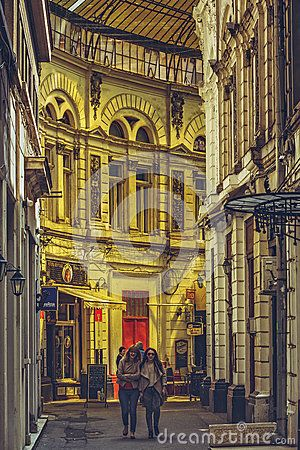 Bucharest, Romania - April 14, 2014: Female tourists stroll the Macca - Villacrosse Passage pedestrian alley, an arcaded street sheltered with yellow glass roof in the historic center of Bucharest.