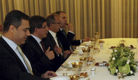 Turkey's intelligence agency chief Hakan Fidan (L) and Foreign Minister Ahmet Davutoglu (2nd L) sit at an iftar table with defected Syrian Gen. Manaf Tlas (not pictured) and other officials in Ankara, July 26, 2012. (photo by REUTERS/Hakan Goktepe/Turkish Foreign Ministry Press Office)