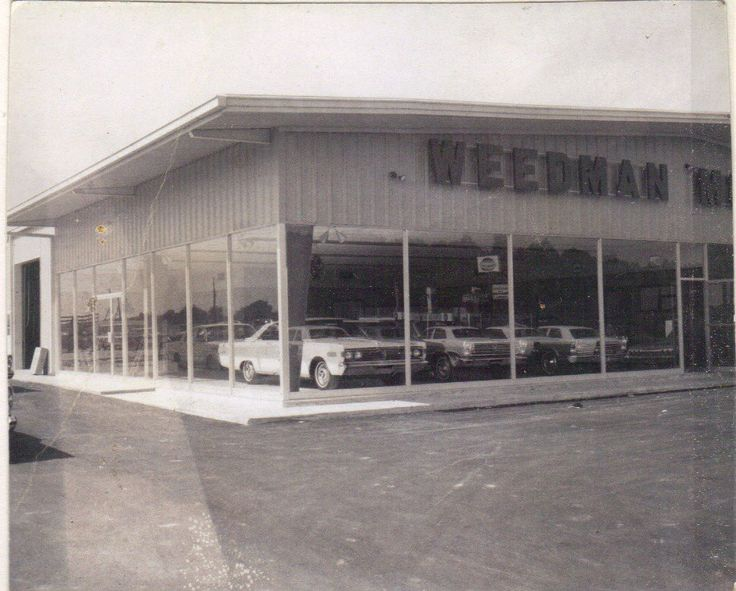 The Ford dealership owned at the time by Mr. Gordon Weedman. It started out as Barnes Automobile on W. 2nd Street, purchased by Mr. Weedman and moved to E. 1st Street in the 50's then to the new, large showroom pictured here. Weedmen Ford was located in the building next to Flowerland Florist.