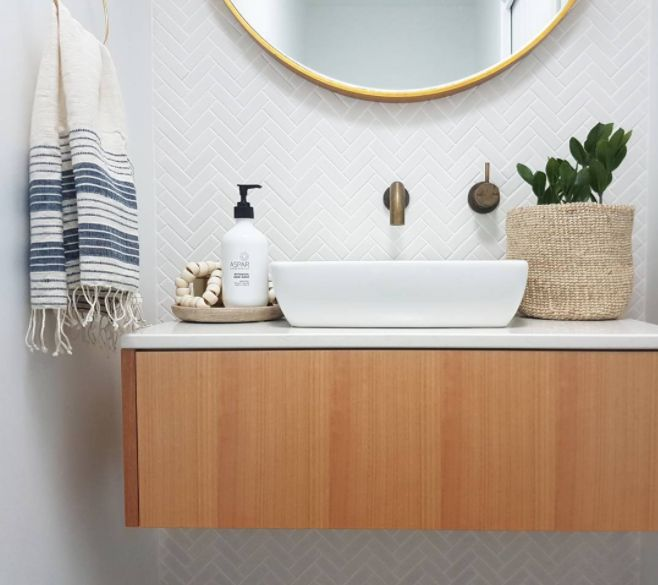 Beautiful powder room with boho styling. Mini white herringbone tile feature wall and brushed brass tapware make the space!