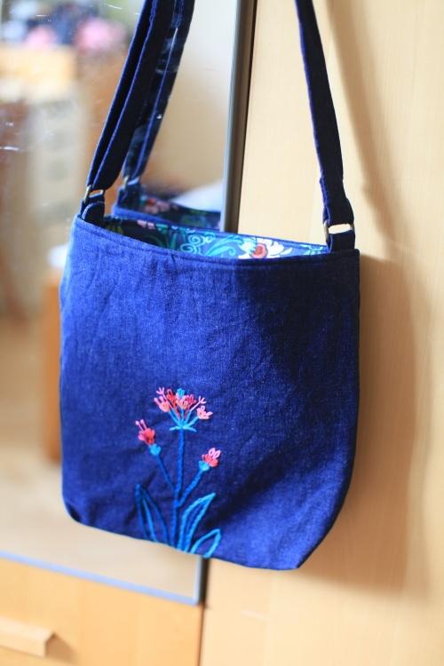 Květinová Kabelka ušitá z modré džínsoviny, po celé ploše vyztužená, podšívka z krásné zahraniční látky. Na přední straně ruční výšivka inspirovaná motivem z podšívky. Nastavitelný popruh. Uvnitř malá kapsička, zapínání na zip. Rozměry: šířka 30 cm, výška 31 cm, hloubka 6 cm