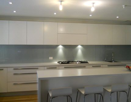 white stone bench, white cupboards, grey/blue tile splash back, door and drawer handles below bench level only