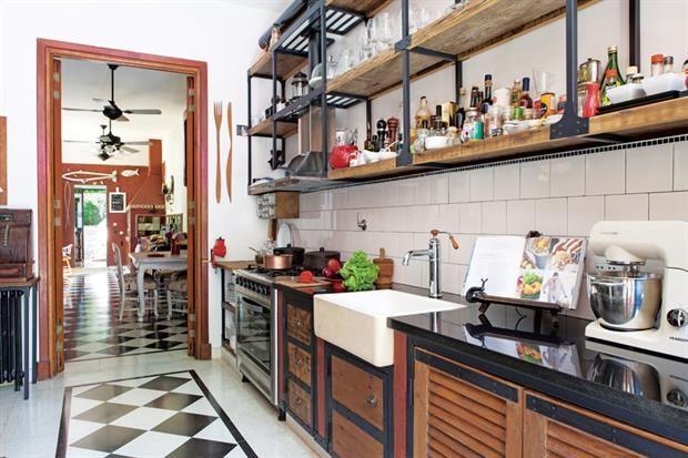 Una cocina diseñada para exponer los tesoros de sus dueños  Para hacer los muebles de cocina (Horacio Manzione) se usaron maderas recuperadas y puertas recicladas. La mesada se hizo con doble mármol negro. Bacha apoyada con grifería vintage 'FV 424' (Barugel) y batidora/ amasadora 'Smartchef' de Peabody (Garbarino)