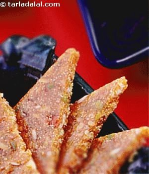 Almond Pistachios Praline Triangles - A delicious praline made of nuts and poppy seeds. A great snack for any time of the day. By Tarla Dalal