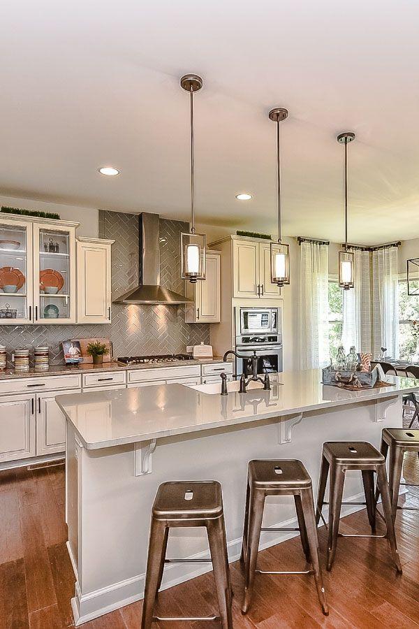 Hardwood Floors, Grey Quartz Countertops, A White Farm Sink, Pendant  Lighting, Metal