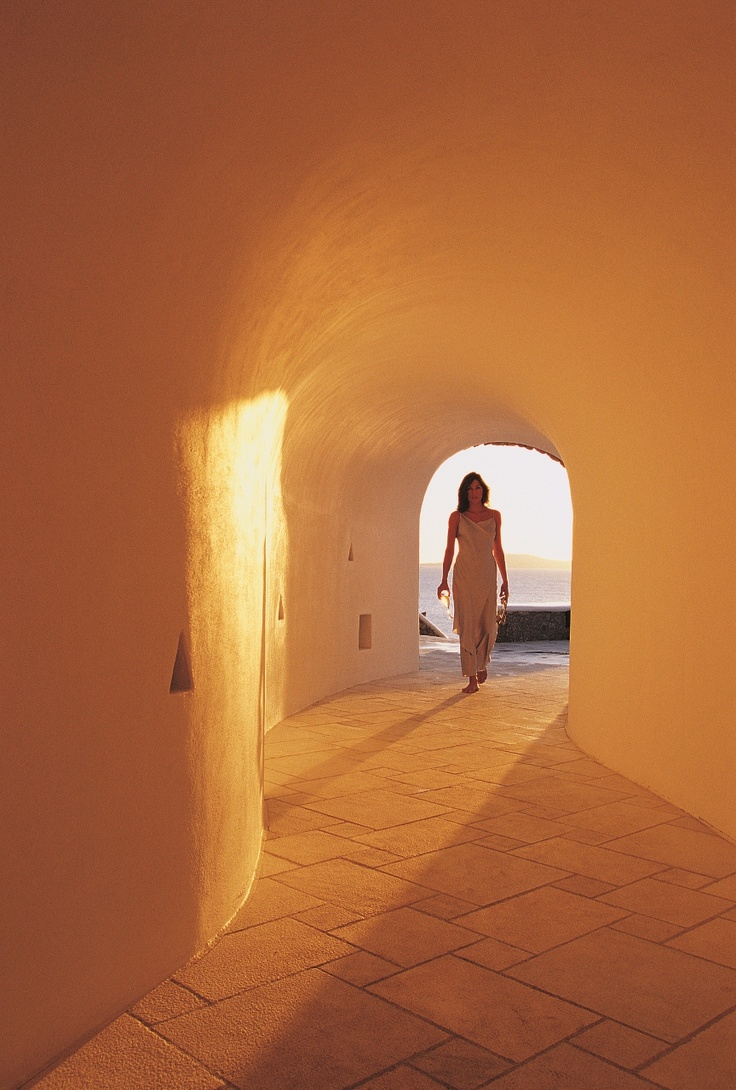 Tunnel at Pool area during cocktail and sunset time with sun rays coloring the white curved walls at Mykonos Grand Luxury Hotel
