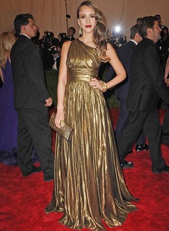 Jessica Alba  Nos encanta el look de Jessica Alba con un vestido de un sólo hombro con cintura marcada y falda plisada en lamé dorado de Michael Kors, con joyas y clutch a juego.