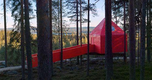 De Blauwe Kegel, die in werkelijkheid knalrood is de meest toegankelijke locatie van het Treehotel. Je bereikt de kamer via een brug vanaf de nabijgelegen berg. De buitenkant is opgetrokken uit gelamineerd berkenhout, het interieur is helemaal van hout.  #origineelovernachten #reizen #origineel #overnachten #slapen #vakantie #opreis #accomodatie #travel #uniek #bijzonder #camping #slapen #hotel #bedandbreakfast #bos #benb #oo #treehotel