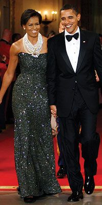 Michelle Obama wearing an extraordinary sequined gown by Peter Soronen topped with a necklace by Tom Binns.