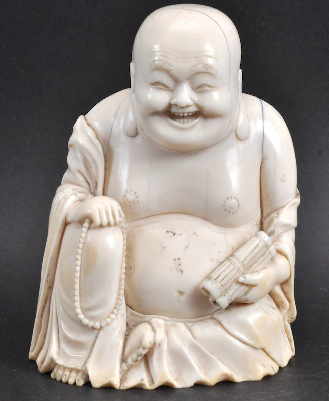A 19TH CENTURY CHINESE CARVED IVORY FIGURE OF A BUDDHA modelled upon a hardwood base.